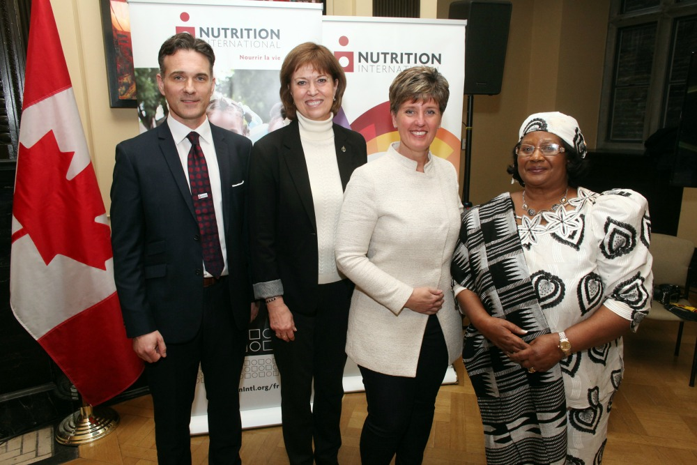 Four people standing inside, beside Canadian flag - from left to right: Joel Spicer, President and CEO of Nutrition International; Pam Damoff, Liberal Member of Parliament; the Honourable Marie-Claude Bibeau, Minister of International Development and La Francophonie; Her Excellency Dr. Joyce Banda, former President of Malawi.