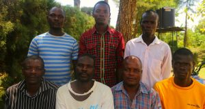 Group of fathers sit outside health centre in Kenya.