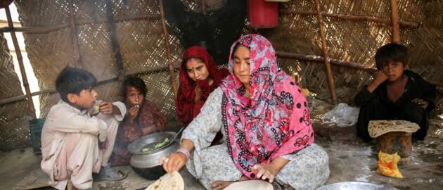 Mother prepares naan for children in Pakistan