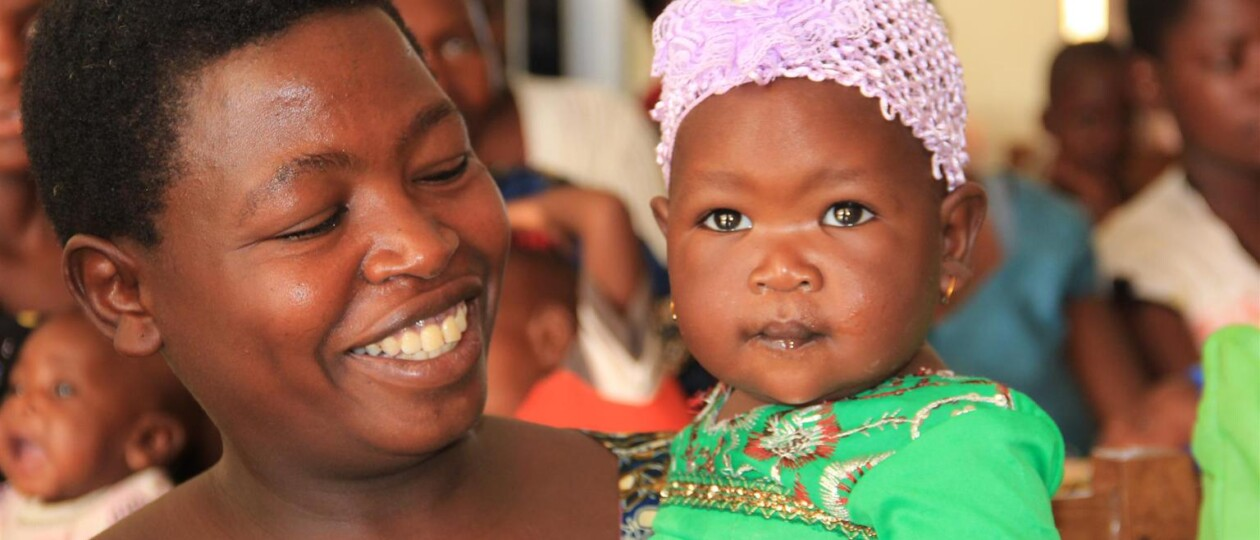Photo of a smiling mother holding her daughter in Tanzania