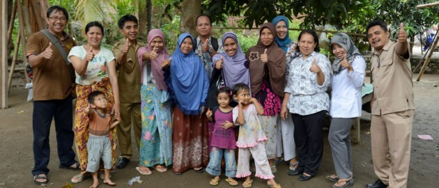 group of people in Indonesia smiling and giving thumbs up