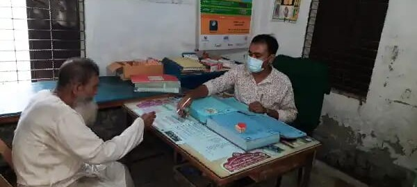 A man with a mask sits across from another man at desk in a health clinic.