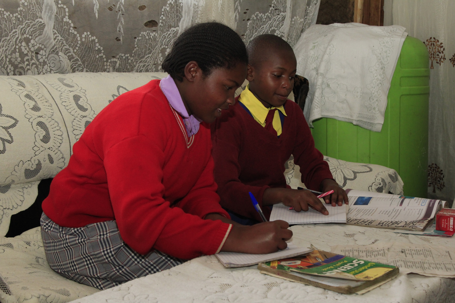 Two girls in school uniforms do their homework in their living room