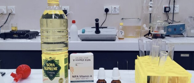 A bottle of cooking oil sits on a counter in a lab beside a rapid testing kit to test vitamin A and D levels in oil.