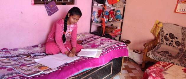 Young woman sits on couch studying in India