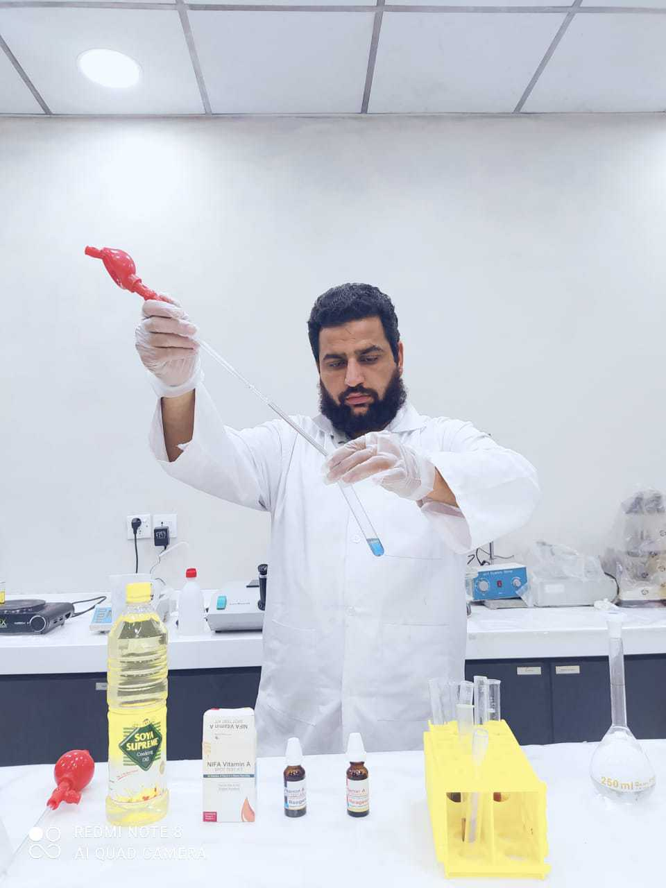 Man in lab coat conducting a vitamin test to check adequacy of fortification in oil