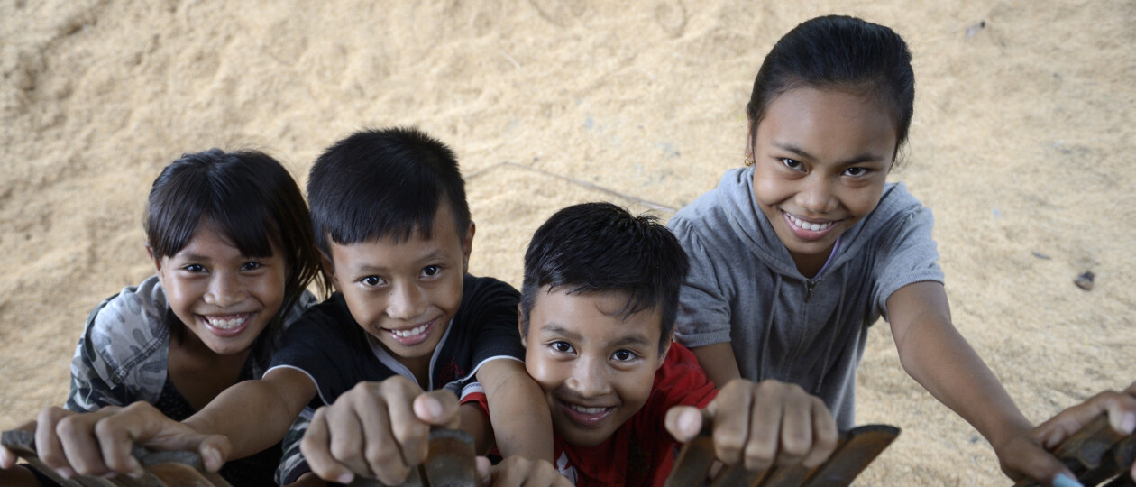 two girls and two boys in Indonesia looking up and smiling