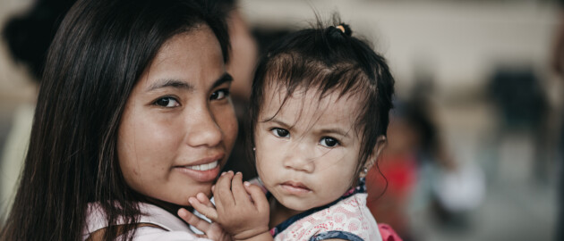 mom holding baby girl in Philippines with both looking at camera