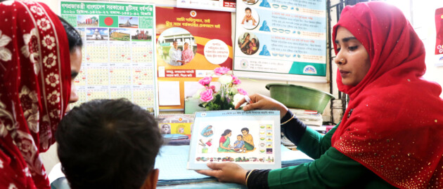 health worker in Bangladesh uses educational materials to explain the importance of health and hygiene to a mother and child