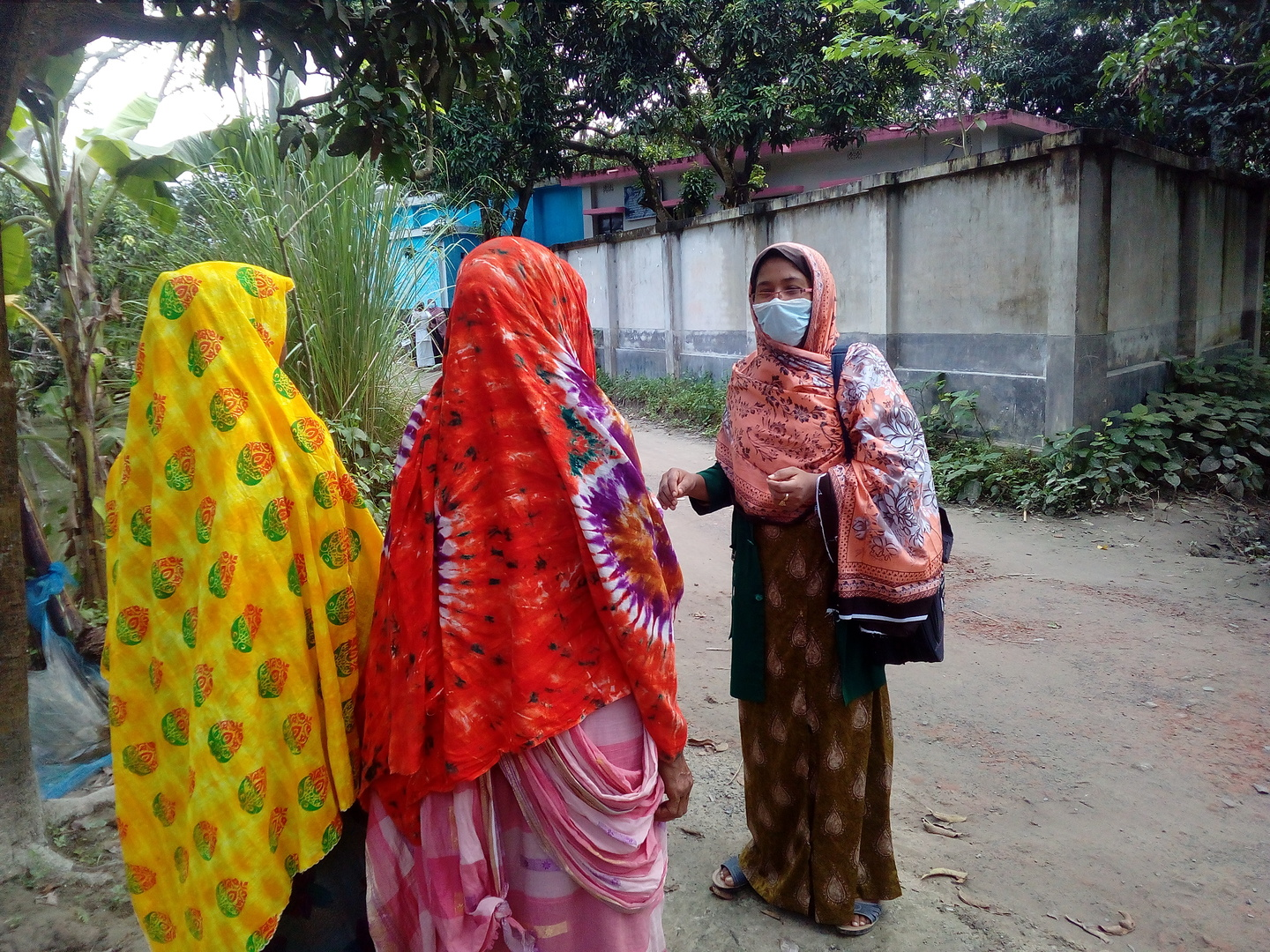 A woman in a medical mask speaks to two women on the street.