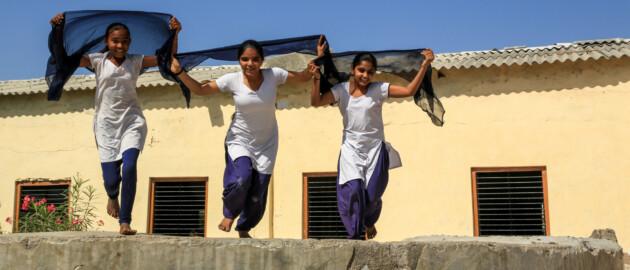 Girls running and jumping in school yard