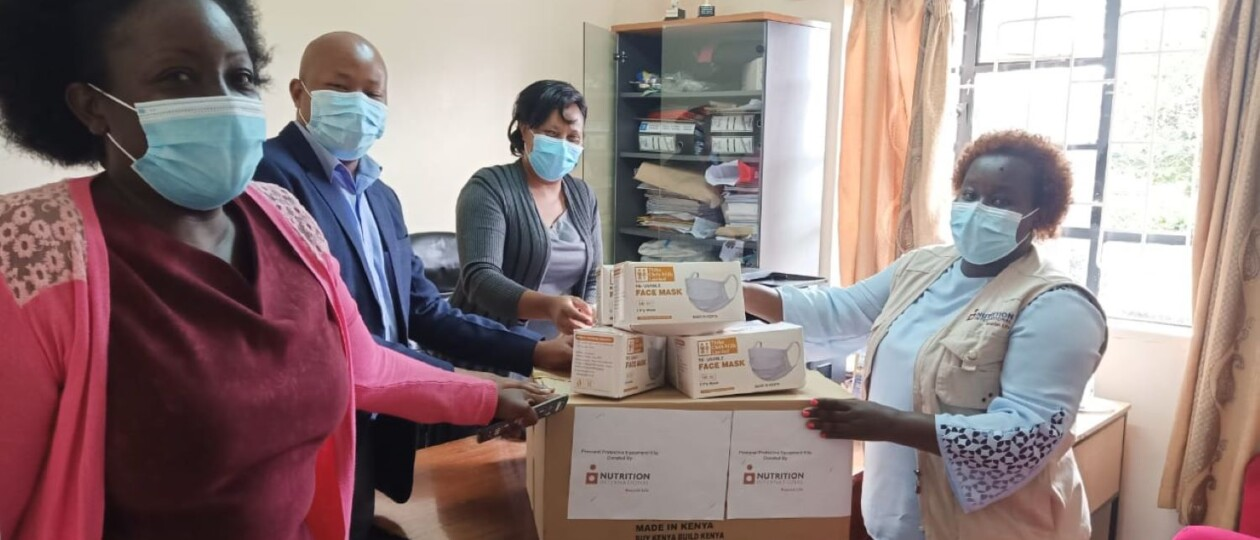 Nutrition International Kenya employees wearing masks standing around boxes of PPE