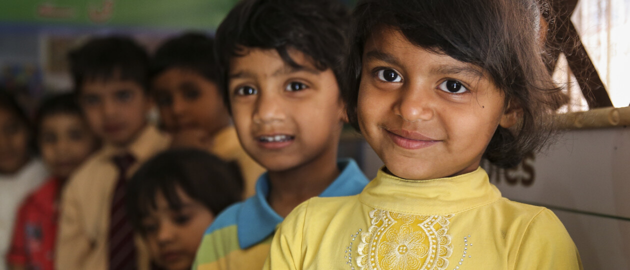 Pakistan boys and girls smiling standing in row in classroom