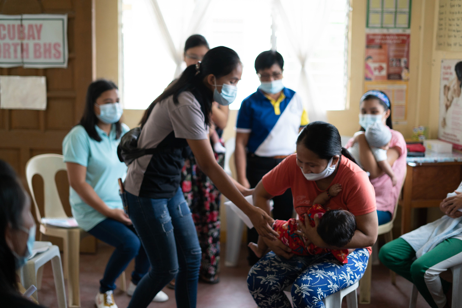 A mother demonstrates different holds for breastfeeding during a peer support group in the Philippines
