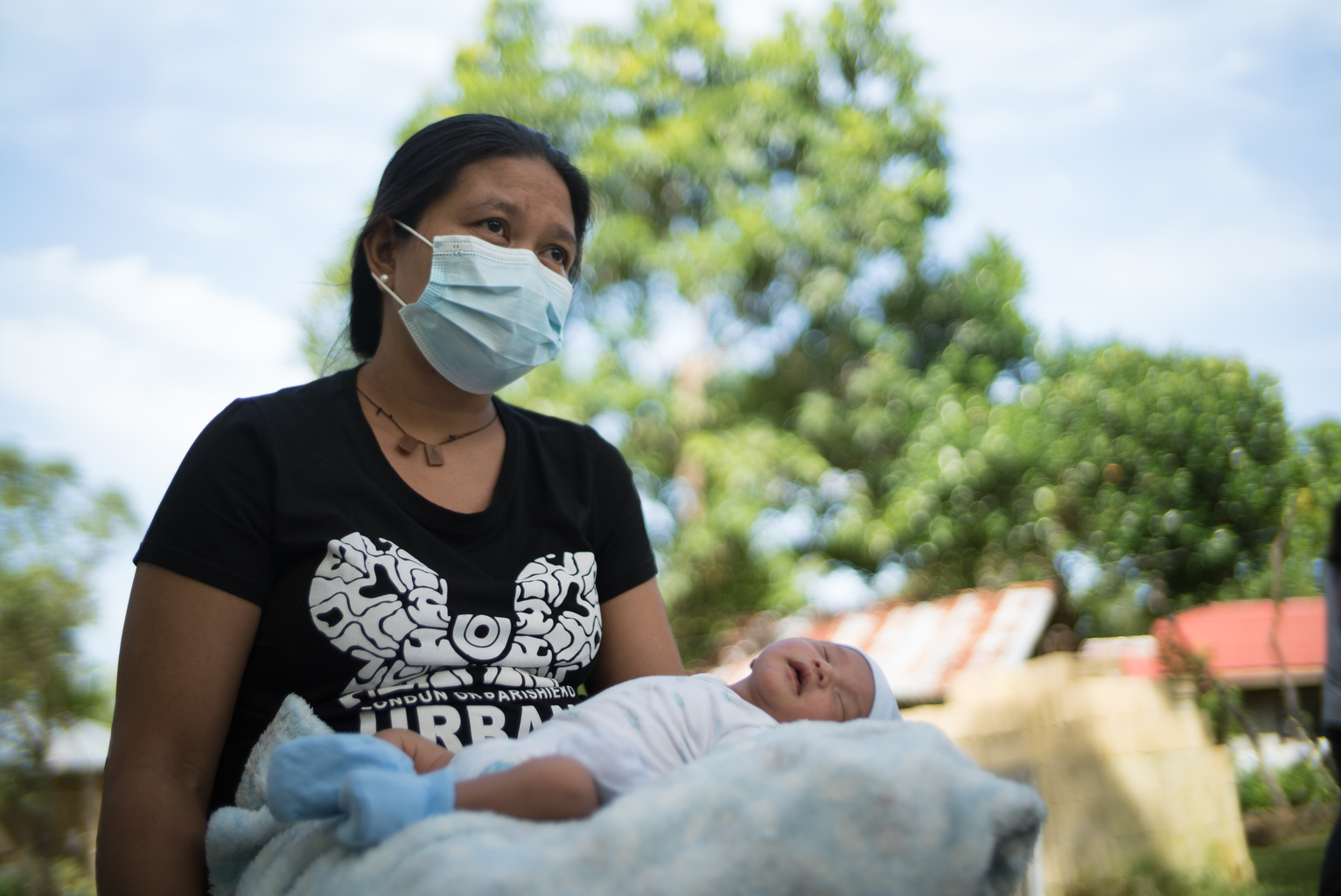 Mother wearing a mask holds her baby