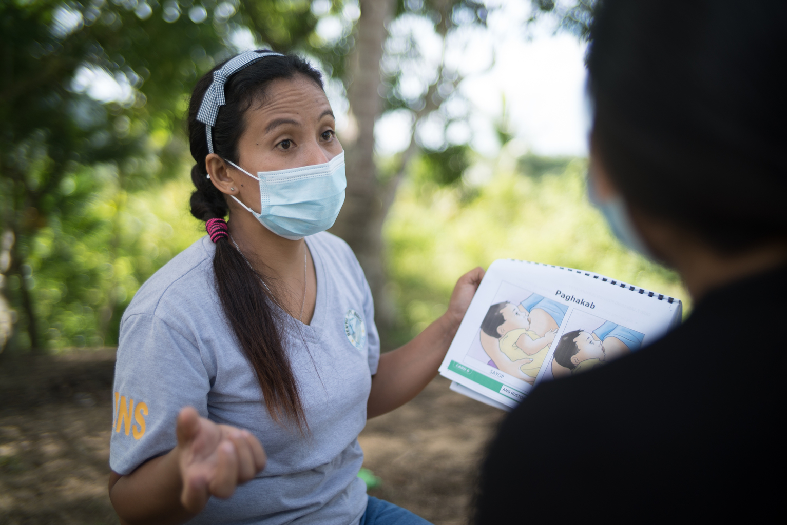 Woman wears a mask outside and holds a booklet during a mother-to-mother support group session in the Philippines
