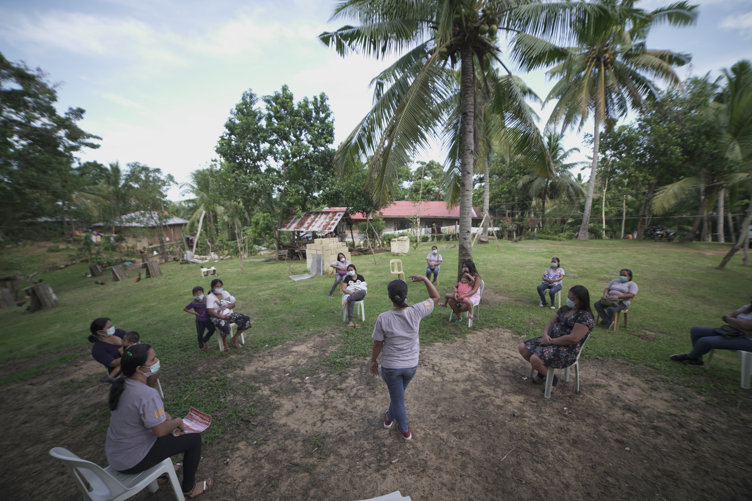 A maternal health trainers speaks to a group outside under palm trees during a mother-to-mother support group in the Philippines