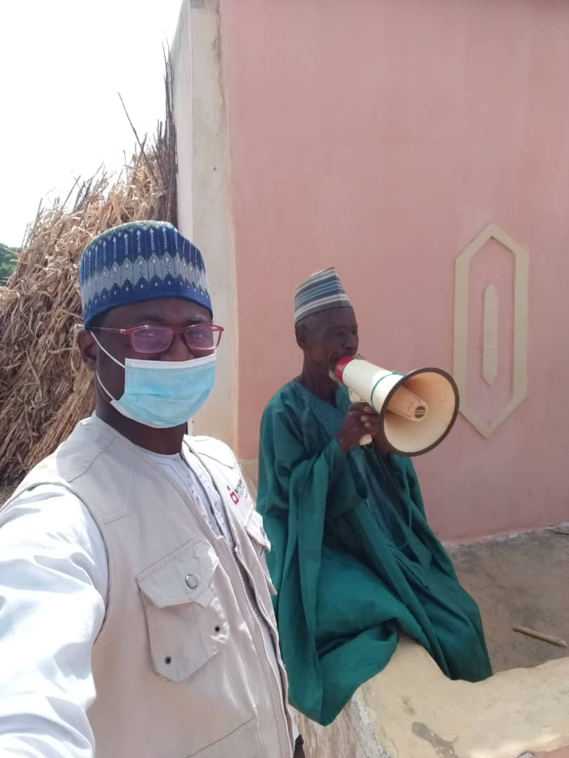 Nutrition International field staff with a town crier mobilizing for a vitamin A distribution in Nigeria