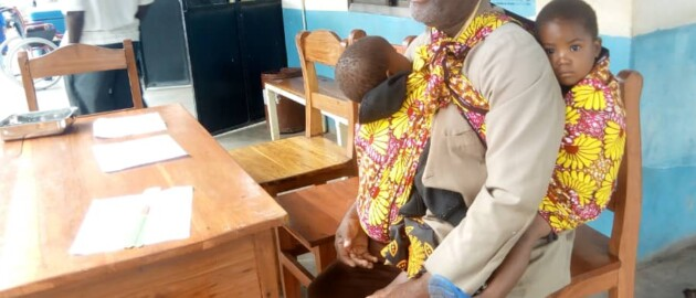 Father sits on a chair at a health clinic carrying his son on his front and holding his daughter behind him.