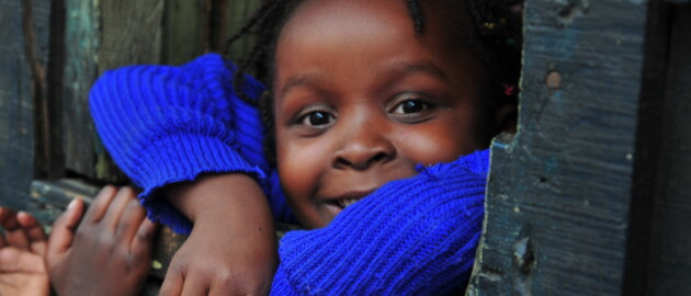 A smiling girl child in Kenya looking through a building opening surrounded by other children
