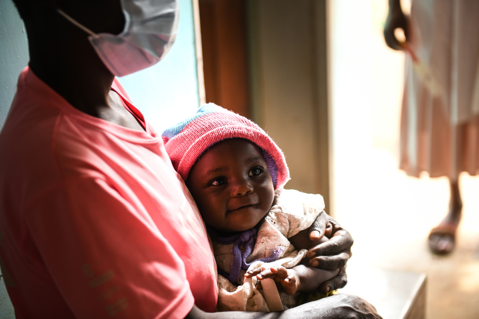An infant wearing a hat smiling in the arms of their mother as they wait to receive a vitamin A dose at Chisitu Health Centre in Mulanje southern Malawi.