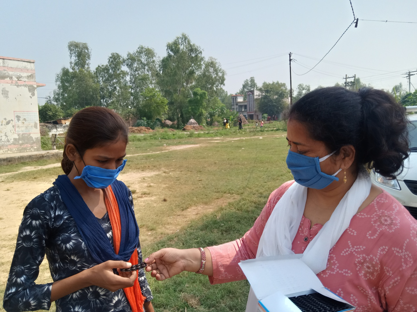 A principal in India stands to the right of a student and hands her a package of iron and folic acid supplements.