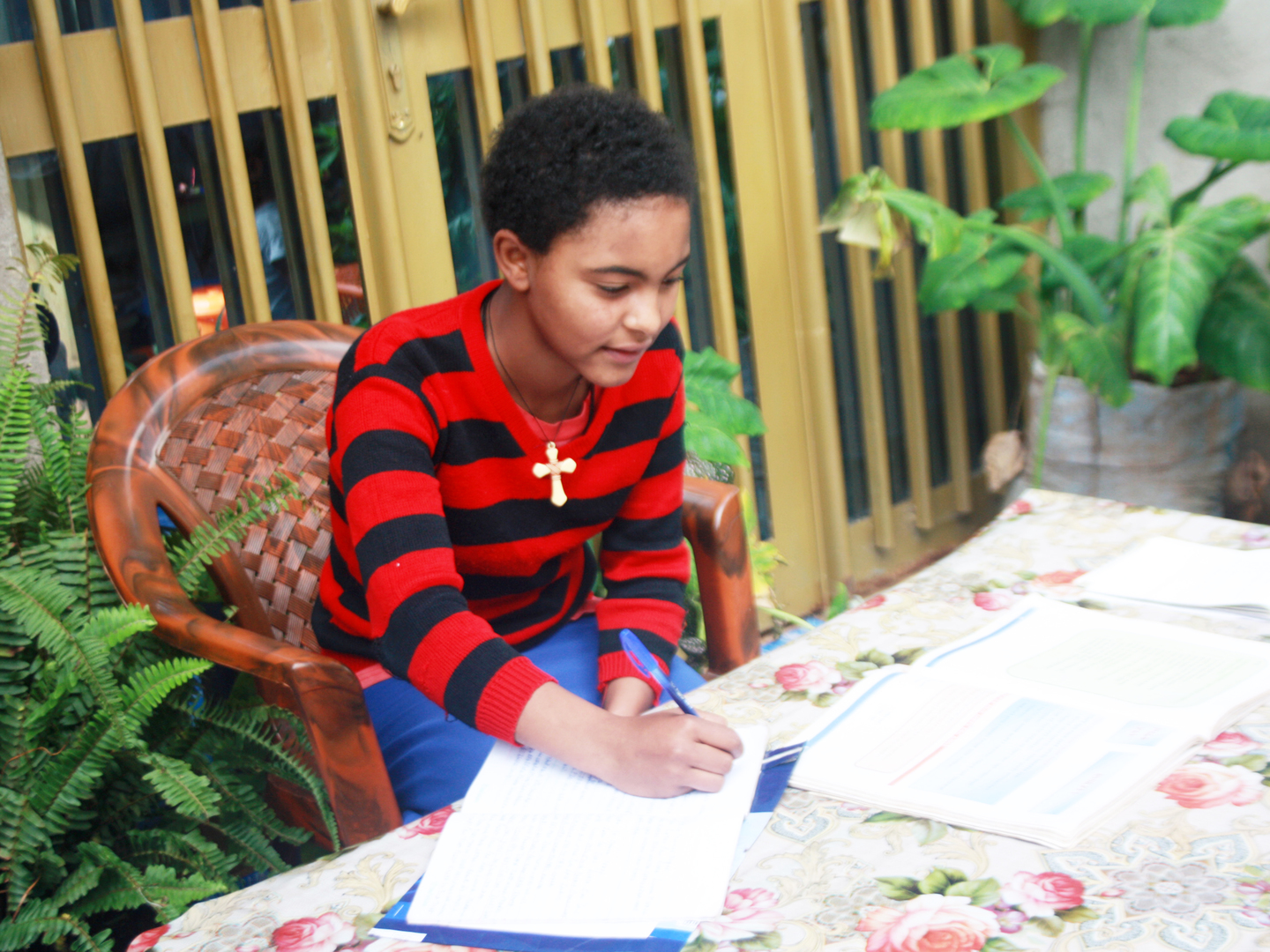 Female student leans over her homework sitting at a table surrounded by plants in Ethiopia
