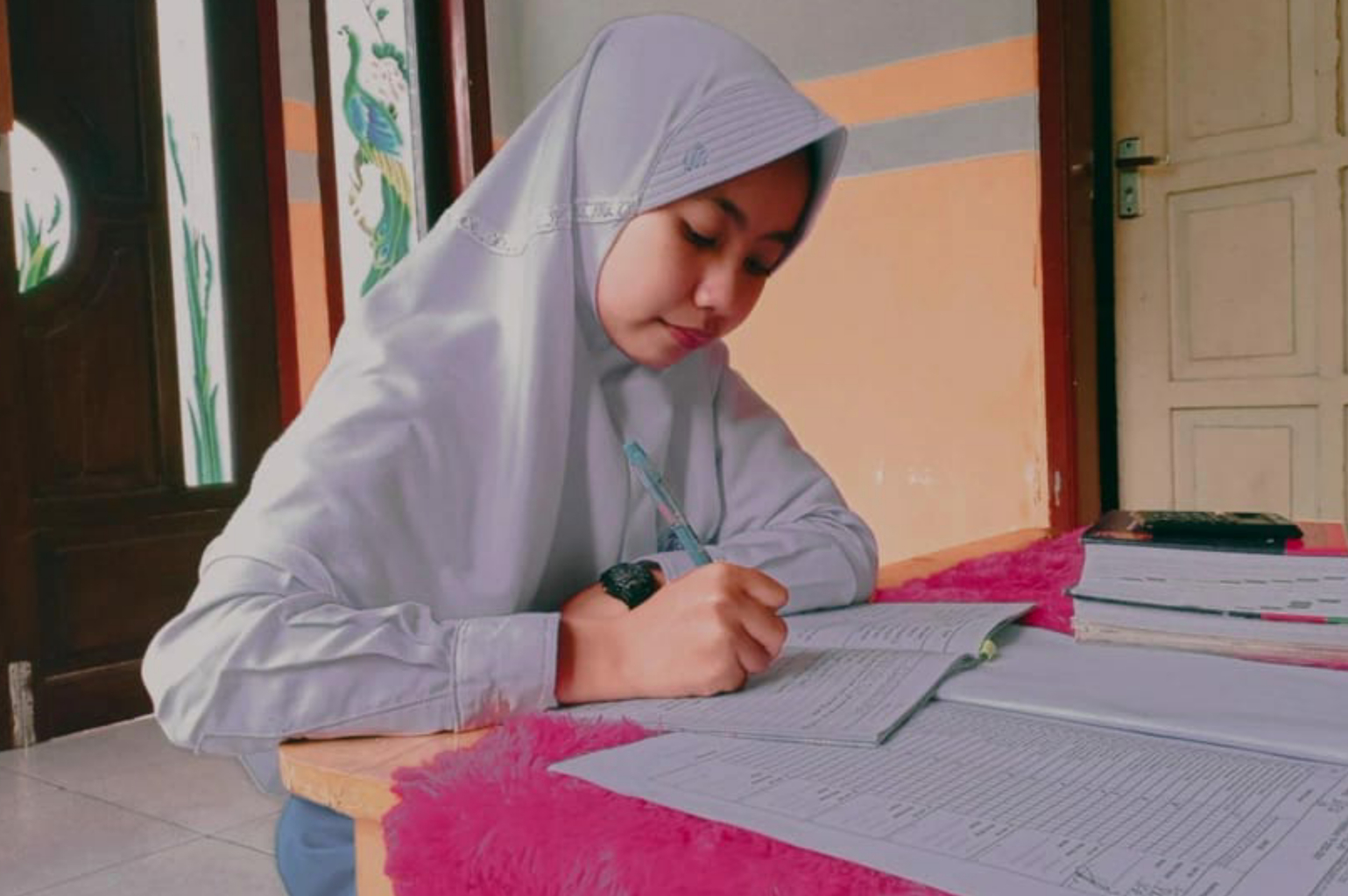 Student in Indonesia sits at a table and does her homework.